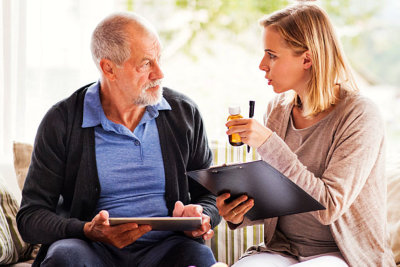 woman giving medication to senior man
