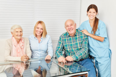 caregivers with senior man and woman smiling