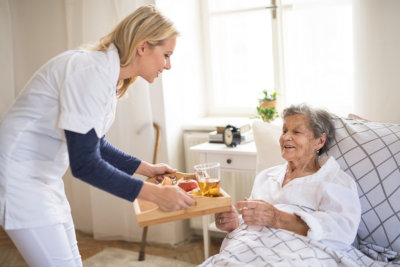 care giver assiting bedridden senior