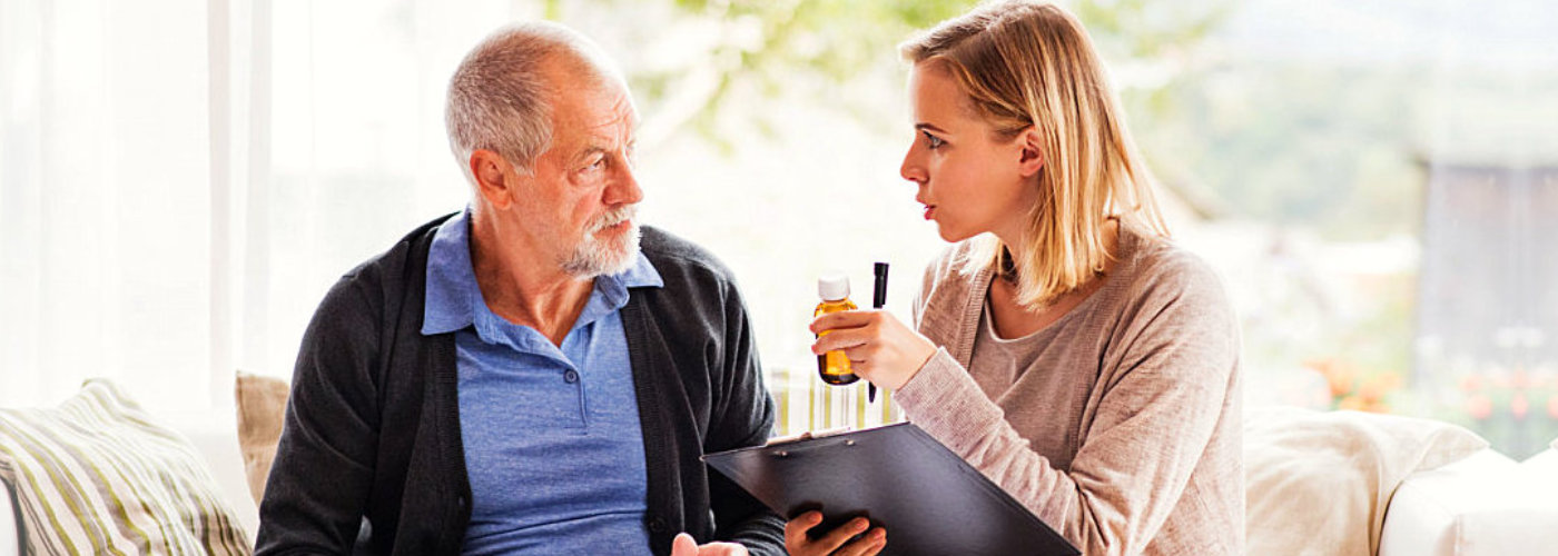 woman giving medication to senior man