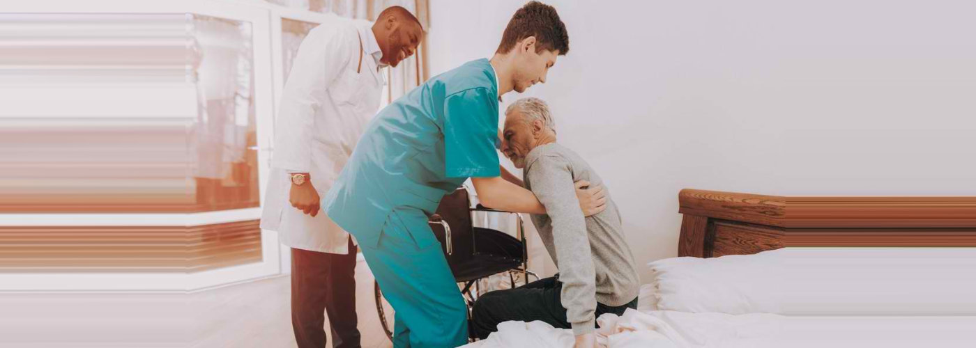 caregiver with a professional helping senior man to get up from bed