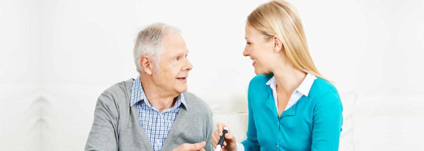 caregiver smiling to a senior man