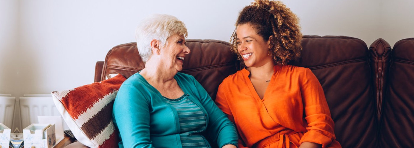 senior woman and a caregiver smiling to each other