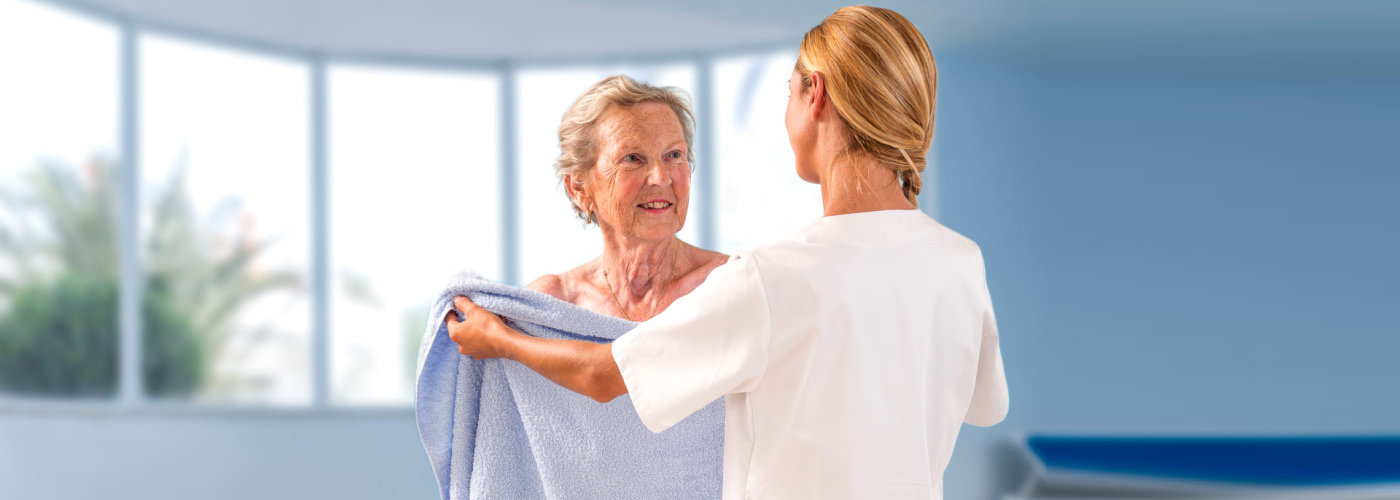 caregiver giving a senior woman a towel